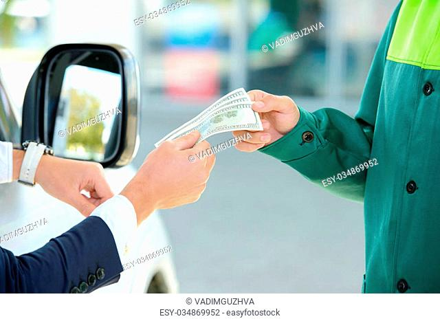 Businessman give money dispensers, filled car on gas station