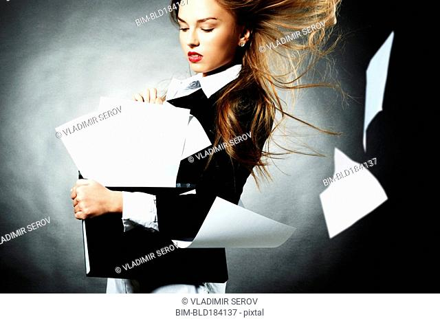 Caucasian teenage girl with windblown papers