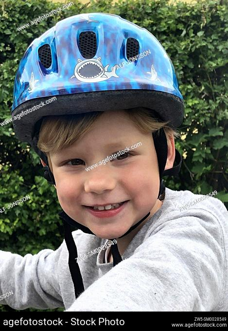 Portrait on a boy, 4 years old, with a bicycle helmet in Ystad, Scania, Sweden; Scandinavia