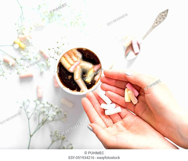 White coffee Cup with colorful marshmallows and small flowers with female hands on white background, concept of drinks and relax