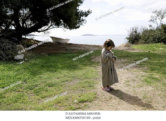 Little girl wrapped in oversized cardigan standing on a meadow