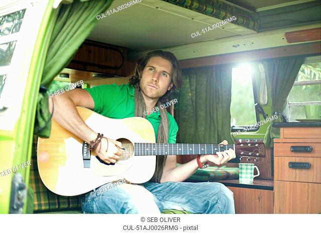 Man playing guitar in trailer