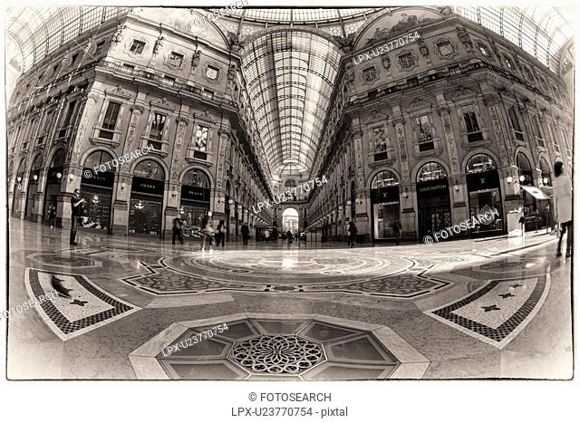 Gallerica Vittorio Emanuele: wide angle view of central mall area , people shopping, glass and cast iron arched roof with stone carving decoration