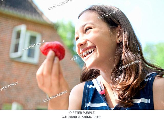 Smiling girl eating outdoors