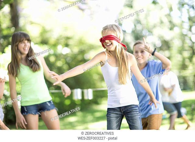 Kids in garden playing blind man's buff