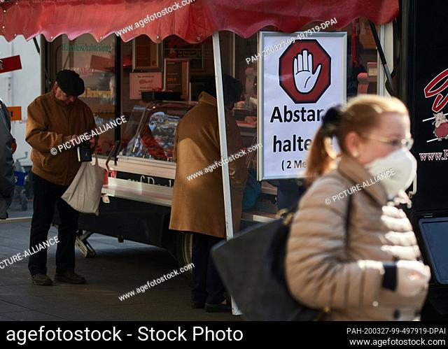 """27 March 2020, North Rhine-Westphalia, Bochum: """"""""Keep your distance!, 2 meters"""""""" a market trader attached a sign to his sausage stand"""