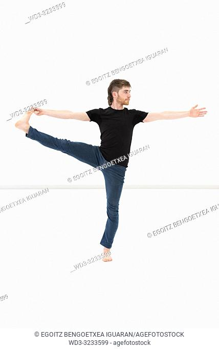 Casual dressed young adult man making yoga exercises on white background