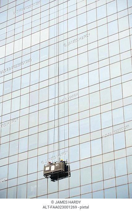 Window washers cleaning side of skyscraper