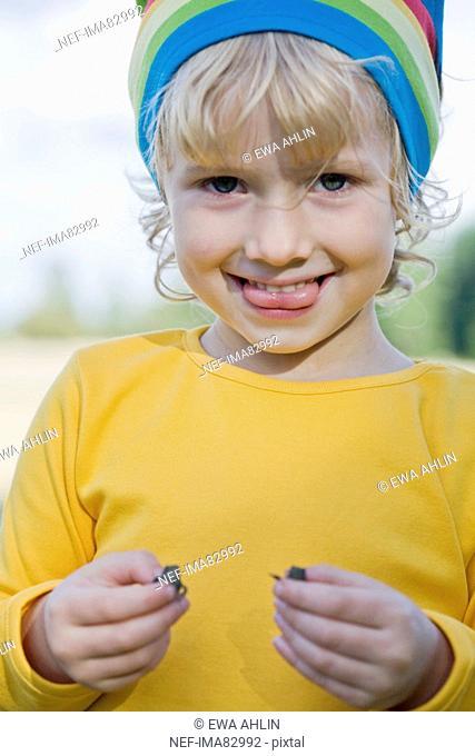 Girl holding frog, smiling