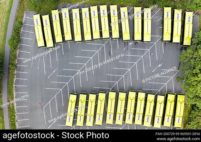 16 July 2020, Saxony, Plauen: An employee of the MAN Bus Modification Center (BMC) walks between hybrid buses across a parking lot