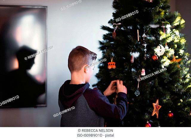 Boy putting up Christmas decorations
