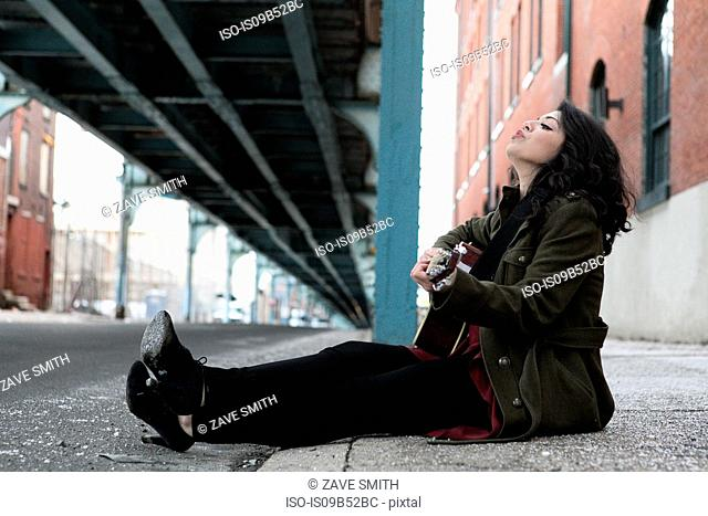 Young woman sitting on city sidewalk playing acoustic guitar