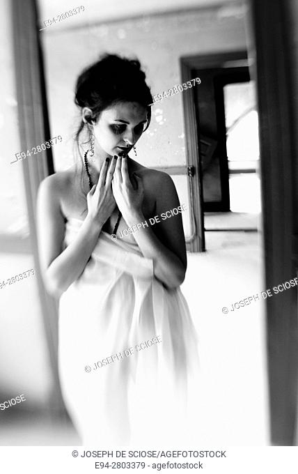 A partially nude 25 year old woman draped in white fabric looking down form the camera standing in an abandoned building, black and white