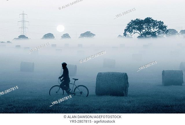 Female mountain biker near Hay bales at sunrise in early morning mist near Billingham, north east England, United Kingdom. United Kingdom