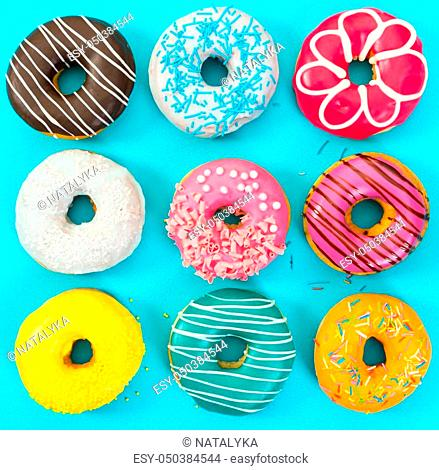 Various colorful donuts on blue background. Top view