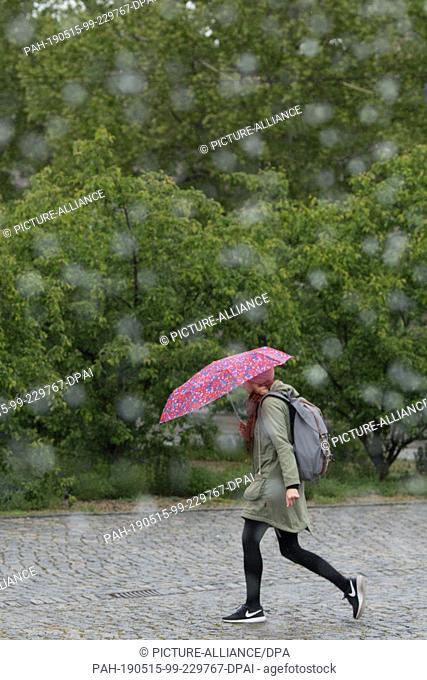 "15 May 2019, Saxony, Dresden: A woman walks under an umbrella behind the fountain """"Water Curtain"""" on the Postplatz. Photo: Sebastian..."