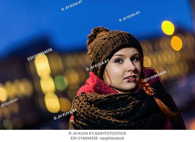 Attractive city woman wearing woolly hat, lights of city on background, focus on foreground