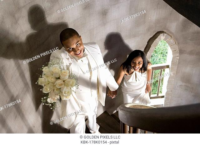 A bride and groom in white climbing up a spiral staircase