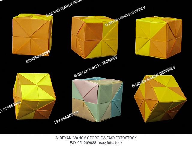 Paper made multi colored patterned cubes folded origami style. Yellow and orange colors