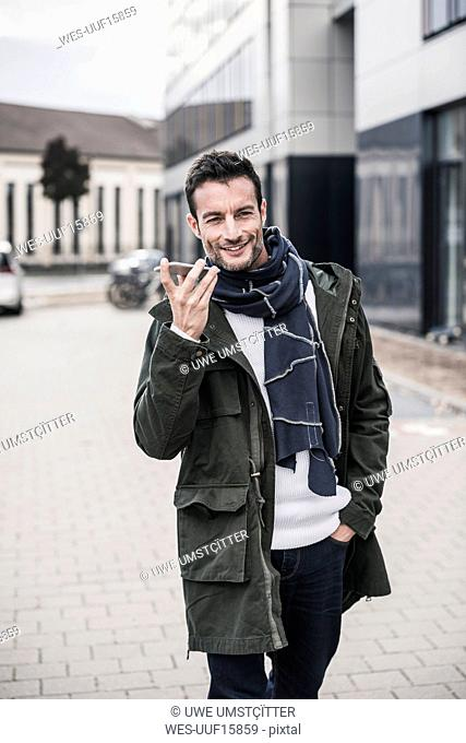 Mature man, wearing coat and scarf, walking in the city, talking on the phone