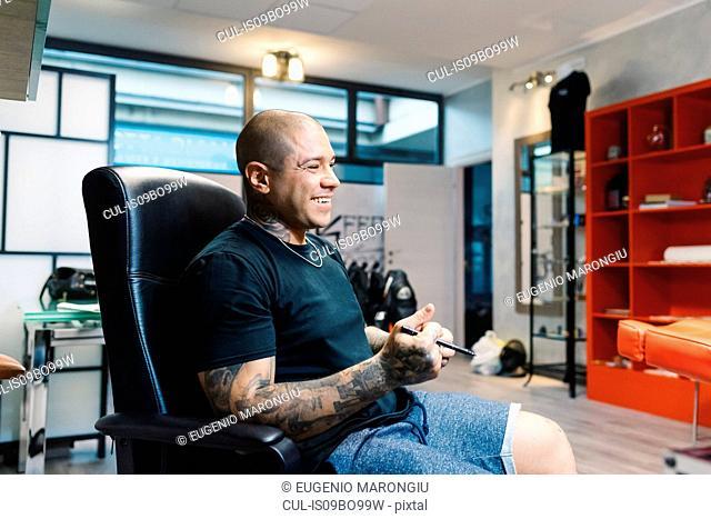Tattooist taking break in parlour