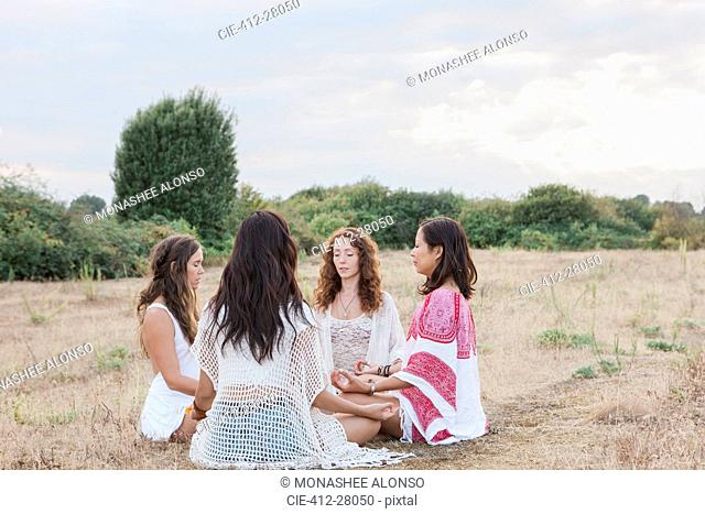 Boho women meditating in circle in rural field