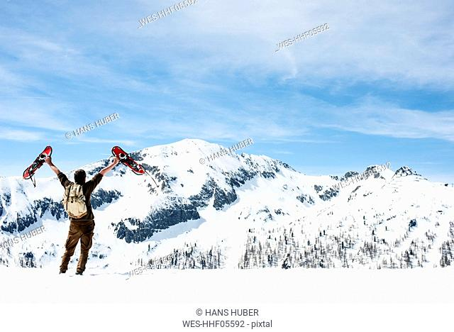 Man with backpack, standing on mountain summit, waving with his snowshoes, rear view, Salzburg State, Austria