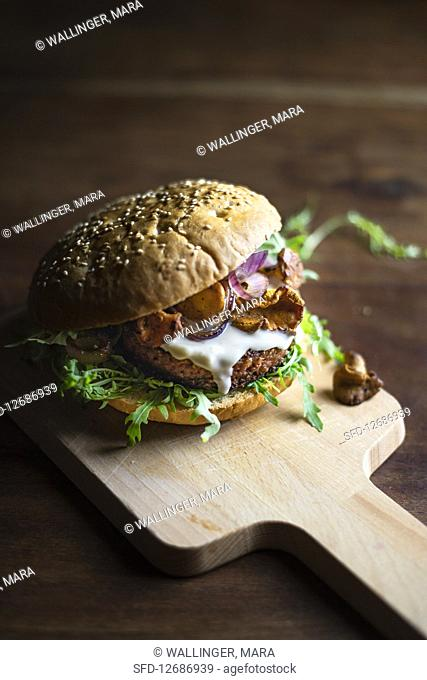Burger with mushrooms and mayonnaise on kitchen board