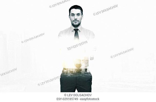business and people concept - handsome businessman with crossed arms over city buildings and double exposure effect