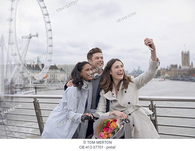 Smiling, happy friends taking selfie with selfie stick on bridge near Millennium Wheel, London, UK