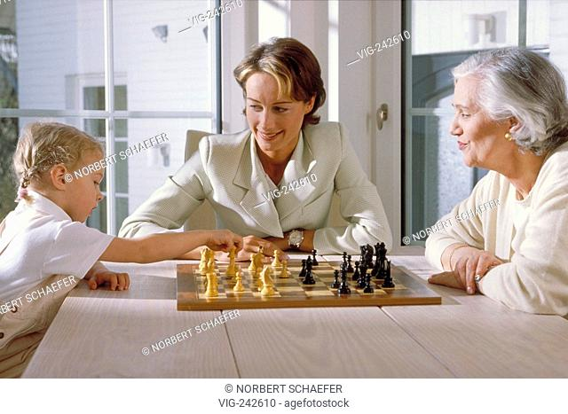 indoor, half-figure, 3 generations, blond girl sits with her mother and her grandmother at a table in front of the window playing chess  - GERMANY, 11/03/2005