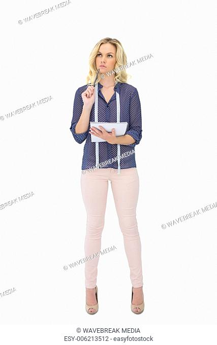 Thoughtful pretty fashion designer holding sketchpad