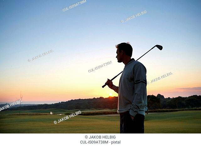 Golfer carrying golf club over shoulder looking at sunset