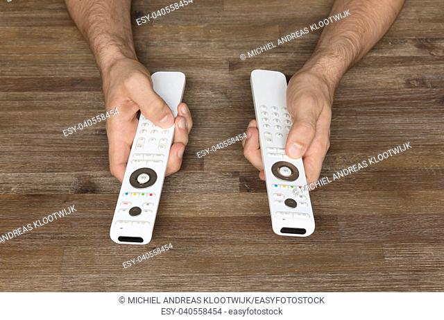 Man holding two white remotes in his hand - Take control!