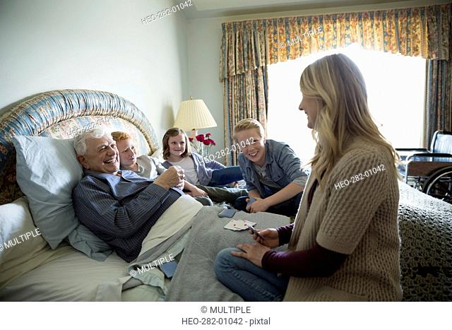 Multi-generation family playing cards with aging grandfather in bed