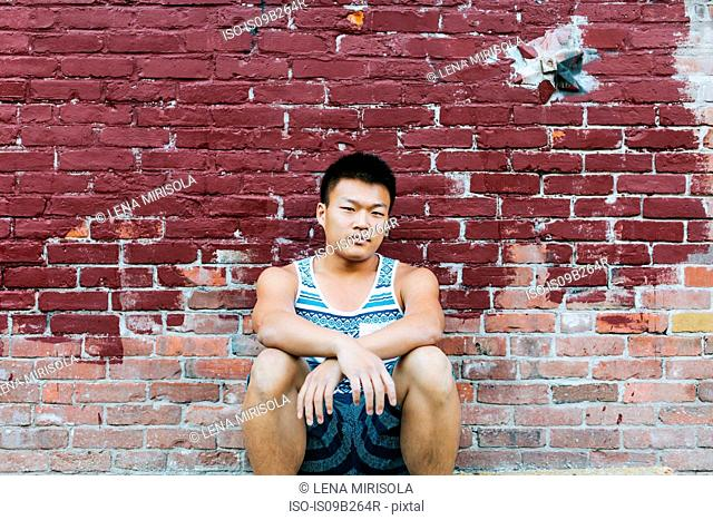 Man squatting in front of brick wall