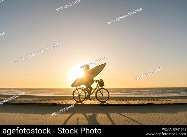 Surfer riding a bicycle during the sunset in the beach, Costa Nova, Portugal