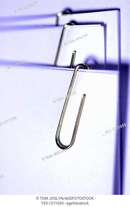 Paperclip on paper in pile close up