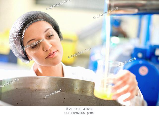 Woman holding beaker of olive oil in olive processing plant