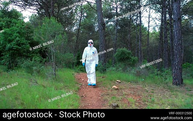 Person with a safety suit walking in a forest area. Ayegui, Navarre, Spain, Europe