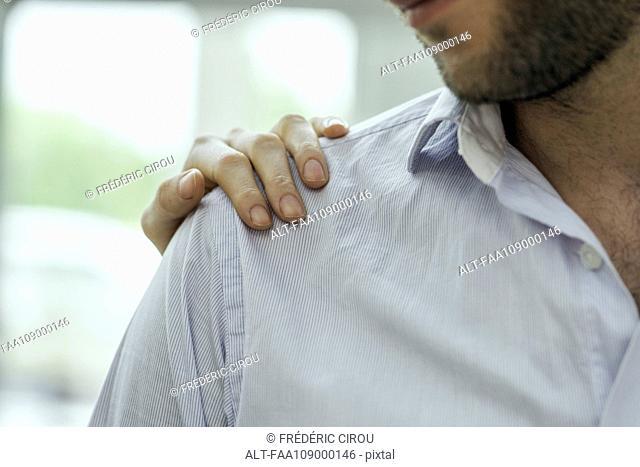 Healthcare worker's hand on patient's shoulder