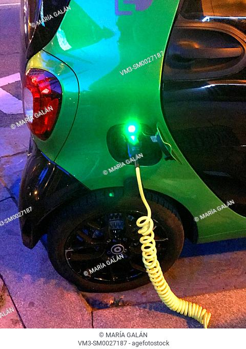 Electric car recharging its battery at night