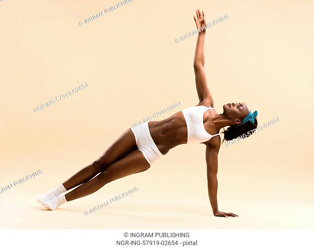 Indoor shot of a young african woman doing yoga