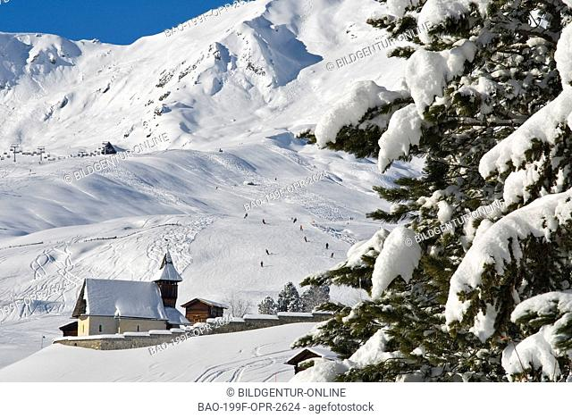 This stock photo shows a typical Swiss mountain church in a Autumn landscape at the small mountain village of Arosa a ski resort in Switzerland
