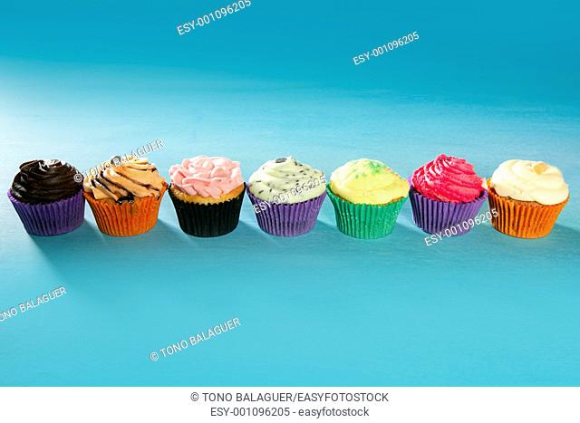 Cupcakes colorful cream muffin arrangement in a row line on turquoise
