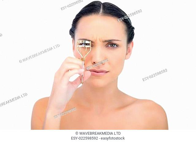 Serious natural brunette with eyelash curler