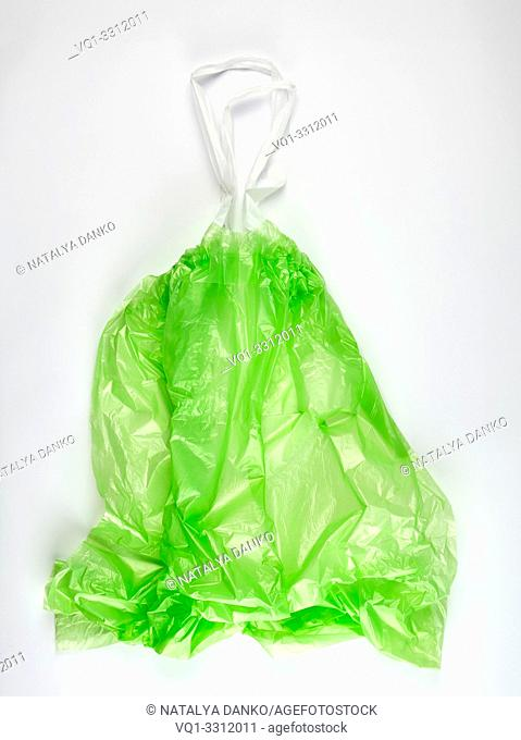 empty transparent green plastic garbage bag with handles on a white background