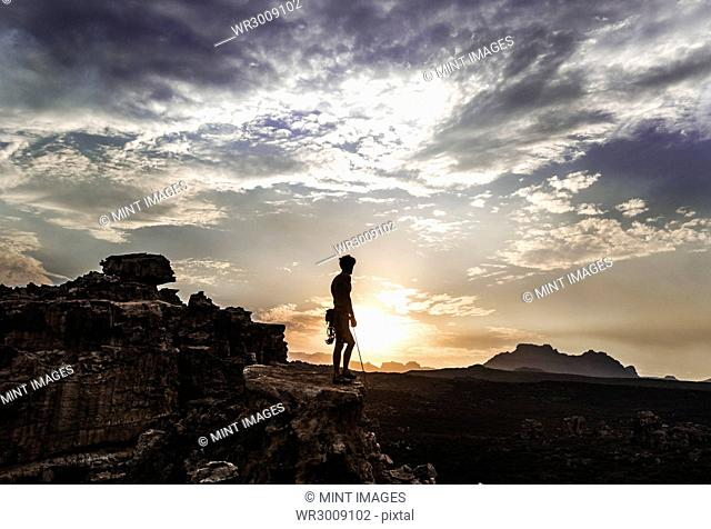 Mountaineer standing on top of a rock formation in a mountainous landscape
