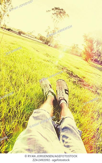 First-person point of view from a man lying down in a shabby green grass field with sun flares and light leak blur. Park life