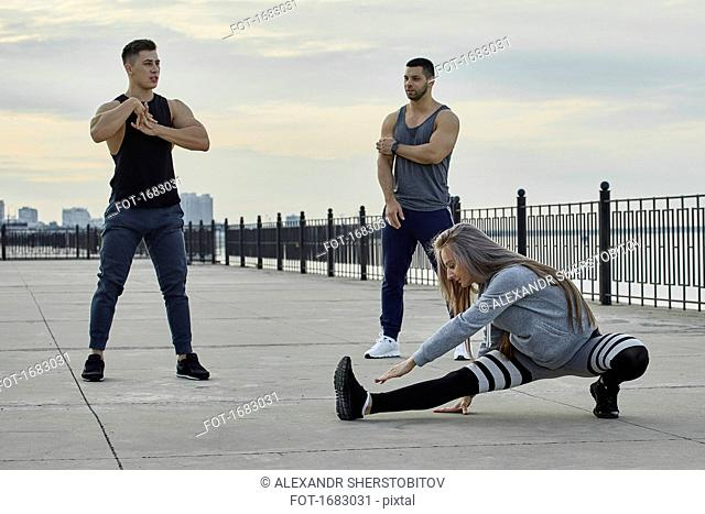 Young athletes stretching on promenade during sunset